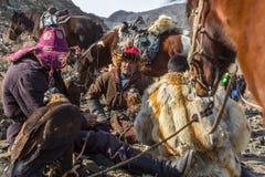 Cazaque Eagle Hunters dourado na roupa tradicional, durante a competição nacional anual com os pássaros do ` de Berkutchi do ` da Fotos de Stock Royalty Free