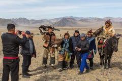 Cazaque Eagle Hunters dourado na roupa tradicional, durante a competição nacional anual com os pássaros do ` de Berkutchi do ` da Foto de Stock Royalty Free