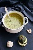 cazo con la sopa poner crema del calabacín y de la espinaca imagen de archivo