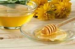 cazo de la miel en una placa de cristal en la tabla de madera Imagenes de archivo