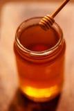 Cazo de la miel y miel de oro en tarro en cierre oscuro del fondo Fotos de archivo