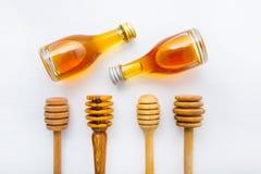 Cazo de madera de la miel y poca botella de la miel en la parte posterior de madera blanca Fotos de archivo