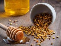 Cazo del polen y de la miel de la abeja con la miel en la tabla Fotografía de archivo libre de regalías