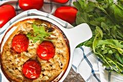 Cazuela con el calabacín, los tomates y los verdes en una servilleta en un wo Imagen de archivo