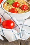 Cazuela con el calabacín, los tomates y los verdes en una servilleta en un wo Fotografía de archivo