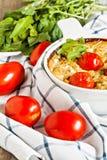 Cazuela con el calabacín, los tomates y los verdes en una servilleta en un wo Foto de archivo libre de regalías