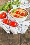 Cazuela con el calabacín, los tomates y los verdes en una servilleta en un wo Imagenes de archivo