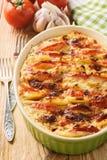 Cazuela de la patata con los tomates, el ajo y el queso Foto de archivo