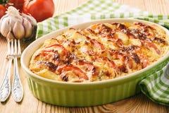 Cazuela de la patata con los tomates, el ajo y el queso Imágenes de archivo libres de regalías