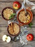 Cazuela o migaja del queso con las manzanas y el canela en ramekin de la taza marrón fotos de archivo