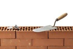 Cazzuola e un piombo Bob su una parete dei mattoni Immagini Stock Libere da Diritti
