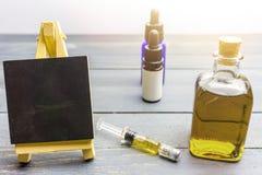 Cbd olja i glasflaska, hampadeg och svart tavla på tabellen arkivfoton