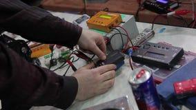 CC$PETERSBURG ROSJA, KWIECIEŃ, - 15, 2010: Mężczyzna ładuje baterie dla rc modelów zdjęcie wideo