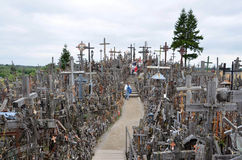 Cca 12 km nord av staden av SIAULIAI/LITAUEN - Juli 24, 2013: Nära sikt av kullen av kors, ett ställe av dyrkan för Chr Royaltyfri Bild