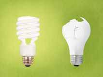 CCFL vs broken regular bulb. Compact fluorescent energy saving environment friendly vs old fashioned broken bulb on green background Stock Photography