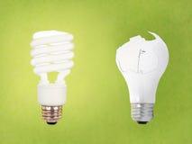 CCFL vs broken regular bulb. Compact fluorescent energy saving environment friendly vs old fashioned broken bulb on green background stock photography