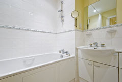 Cclassic sttyle bathroom. Classic style bathroom with white ceramic suite and yellow wall paint stock images