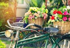 Cclose επάνω στο εκλεκτής ποιότητας ποδήλατο με τα λουλούδια ανθοδεσμών στο καλάθι Στοκ φωτογραφία με δικαίωμα ελεύθερης χρήσης