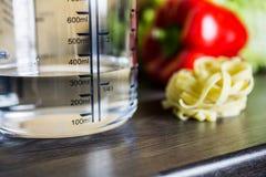 300ccm/300ml da água no copo de medição de A em um contador de cozinha com alimento Foto de Stock Royalty Free
