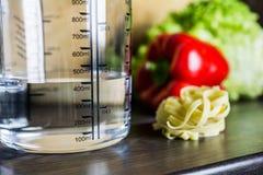 400ccm/400ml da água no copo de medição de A em um contador de cozinha com alimento Fotografia de Stock Royalty Free