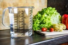 900ccm/900ml da água no copo de medição de A em um contador de cozinha com alimento Imagem de Stock Royalty Free
