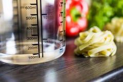 100ccm/100ml de l'eau dans la tasse de mesure d'A sur un comptoir de cuisine avec la nourriture Photo stock