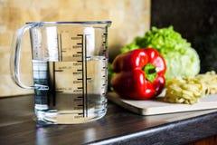 700ccm/700ml des Wassers in einem Messbecher auf einer Küchenarbeitsplatte mit Lebensmittel Lizenzfreie Stockfotografie