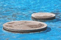 CCoseup av betong som kliver stenar i blåttpöl Royaltyfria Foton
