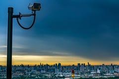 CCTV监视,安全监控相机 背景有城市的看法在美好的微明期间的 免版税库存照片