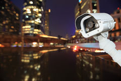 CCTV with bokeh blurring city in night background. Stock Images