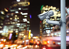 CCTV camera with blurring the night city in background. Royalty Free Stock Photos