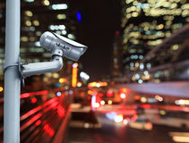 CCTV camera with blurring the night city in background. Royalty Free Stock Images