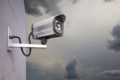 CCTV Camera with clouds. CCTV Camera attached to wall with clouds Royalty Free Stock Images