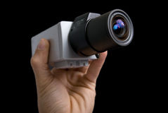 Cctv camera in hand. On black background stock photo