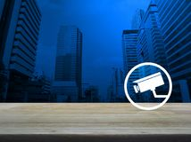 Business security concept. Cctv camera icon on wooden table over modern office city tower background, Business security concept royalty free stock images