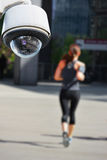 CCTV camera with jogger. Security CCTV camera or surveillance system with jogger on blurry background Stock Image