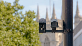 CCTV Camera in London. Attached to post with blurry tree and church tower in background stock photography