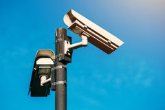CCTV camera, modern era anti-terrorist electronic surveillance. Security cameras against blue sky that symbolizes freedom Royalty Free Stock Photos