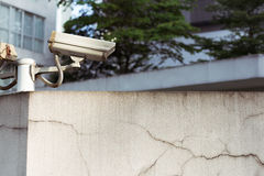 CCTV camera mounted on top of a wall watching over an area. royalty free stock photos