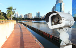 CCTV camera or surveillance operaiting with building and park in. Background Stock Photo
