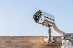 CCTV camera on wooden wall against sky Royalty Free Stock Photo