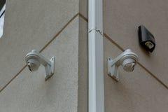 CCTV-kamera för två vit på den vita väggen arkivbilder