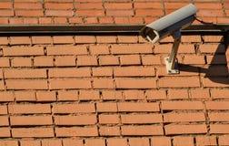 Cctv-kamera utomhus på en tegelstenvägg Arkivfoto