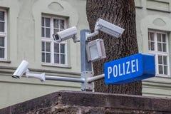 Cctv-kameror på skärm bredvid en polisstation med polisen undertecknar in tysk: Polizei i den bayerska staden av Munich Royaltyfria Foton
