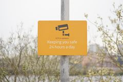 CCTV in operation sign 24 hours a day keeping you safe security sign post orange minimal royalty free stock photo