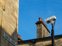 CCTV on pole looking down street through buildings. CCTV camera in silhouette on pole looking down Common Garden Street in Lancaster UK.  Light Sandstone Stock Photo