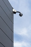 Cctv-säkerhetskamera på fasad av byggnad Arkivbilder