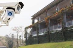 Cctv-säkerhetskamera som fungerar på trädgården som taklägger huset Arkivbild