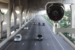 CCTV security camera on blurred of traffic road background Stock Images