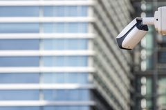 CCTV security camera on building wall in front skyscraper stock photo